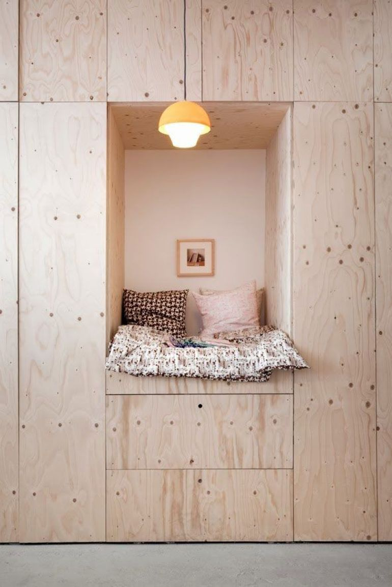 birch plywood storage wall with a reading nook